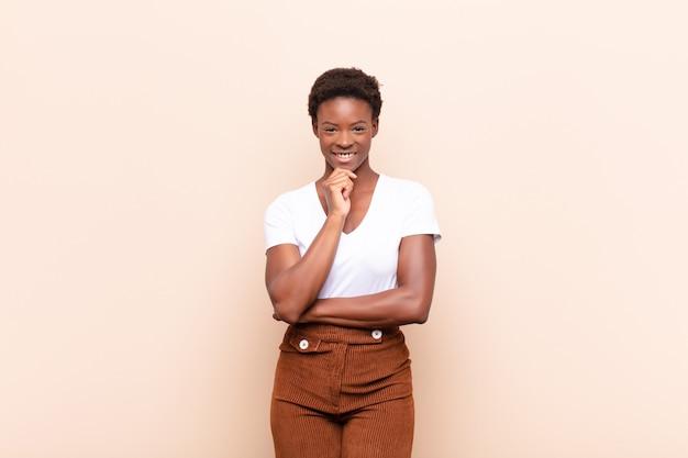 Er blij uitzien en glimlachen met de hand op de kin, zich afvragen of een vraag stellen, opties vergelijken