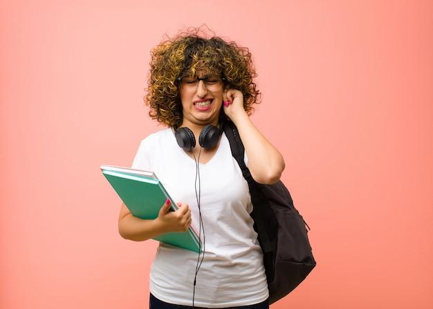 Er boos, gestrest en geïrriteerd uitzien, beide oren bedekkend voor een oorverdovend geluid, geluid of luide muziek