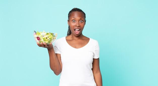 Er erg geschokt of verrast uitzien en een salade vasthouden