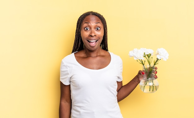 Er erg geschokt of verrast uitzien, starend met open mond en wow zeggend. decoratief bloemenconcept