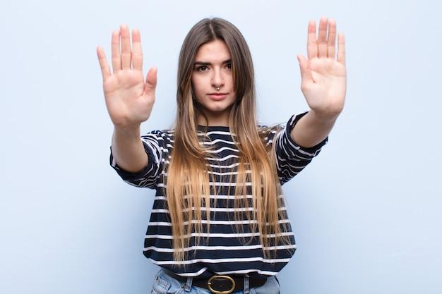 Er ernstig, ongelukkig, boos en ontstemd uit te zien en de toegang te verbieden of te stoppen met beide open handpalmen