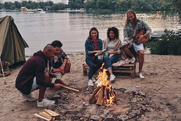 Er even helemaal tussenuit... groep jonge mensen in vrijetijdskleding die lacht terwijl ze genieten van een strandfeestje bij het kampvuur