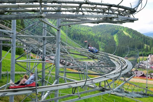 Er is een achtbaanrit op de zomerhelling van de berg. twee kraampjes met mensen dalen erlangs af, tegen een onscherpe achtergrond. mensen zijn onpersoonlijk