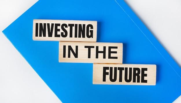 Er is een blauw notitieboekje op een lichtgrijze achtergrond. hierboven staan drie houten blokken met de woorden investeren in de toekomst.