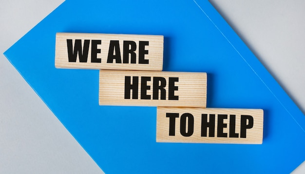 Er is een blauw notitieboekje op een lichtgrijze achtergrond. hierboven staan drie houten blokken met de woorden we zijn hier om te helpen.