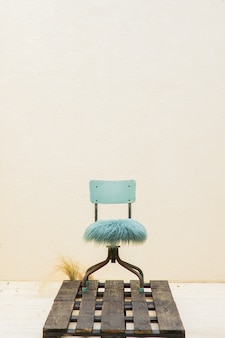 Er is een blauwe stoel op een vintage gele achtergrond een zwarte boom op de vloer