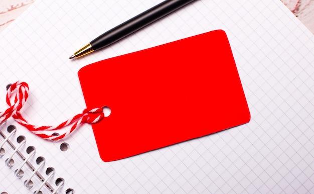 Er is een pen en een rood gekleurd prijskaartje aan een touwtje met een plek om tekst in te voegen op een wit notitieboekje.