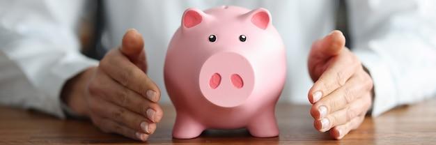Er is een roze spaarvarken in menselijke handen. bevoegde opslag van fondsen.