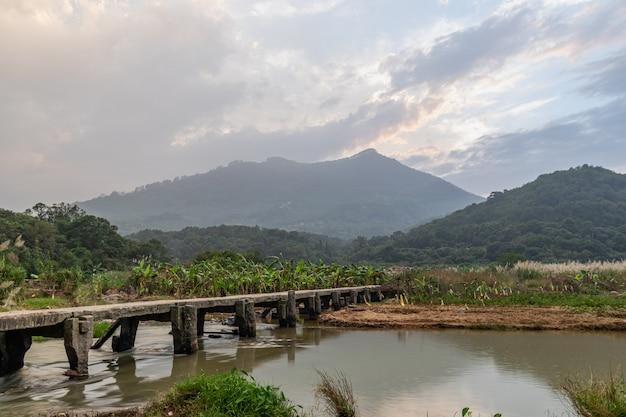 Er is een stenen brug aan de voet van de berg. onder de stenen brug is een beekje