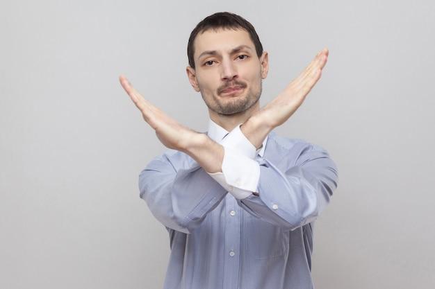 Er is geen manier. portret van een knappe zakenman met borstelharen in een klassiek lichtblauw shirt dat naar de camera kijkt met een afwijzingsblok x-teken. indoor studio-opname, geïsoleerd op een grijze achtergrond copyspace