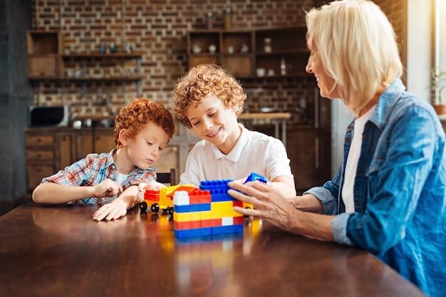 Er is geen plaats zoals thuis. selectieve focus op lachende broers met krullend haar die met bouwstenen spelen en auto's construeren