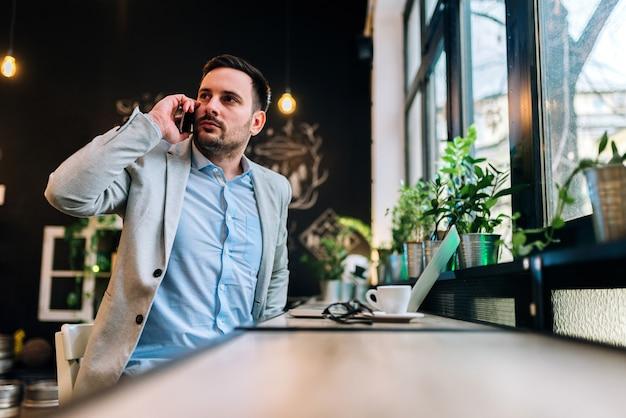 Er is iemand te laat. ernstige zakenman die een telefoongesprek heeft bij het restaurant.