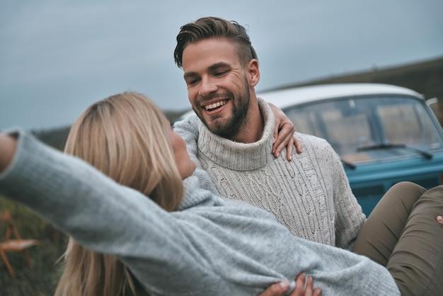 Er is liefde in de lucht! knappe jonge man die zijn aantrekkelijke vriendin draagt en glimlacht terwijl hij met de blauwe retro-stijl minibus op de achtergrond staat