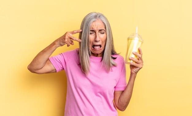 Er ongelukkig en gestrest uitzien, zelfmoordgebaar maakt een pistoolteken met de hand, wijst naar het hoofd en houdt een milkshake vast