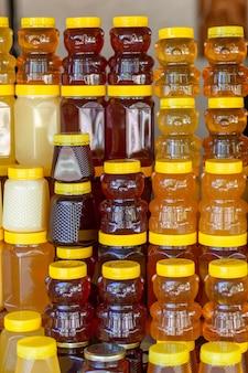 Er staan veel potjes biologische, natuurlijke honing op de toonbank te koop. verschillende honing, verschillende kleuren in plastic blikjes staan klaar voor verkoop op de honingbeurs. noten gevuld met honing.