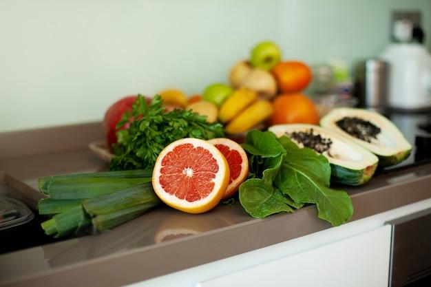 Er staan verse groenten en fruit op tafel.