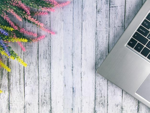 Er staat een computer op tafel, ernaast staat een boeket lavendel.