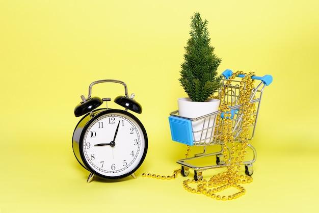 Er staat een kunstkerstboompje en gouden kralen in de winkelwagen een zwarte wekker...