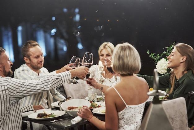 Er was een grote deal gebeurd. succesvolle tost. groep volwassen vrienden hebben 's avonds een rust en een gesprek in de achtertuin van het restaurant.