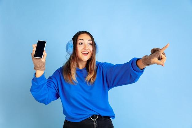 Er wordt een leeg scherm weergegeven. het portret van de kaukasische vrouw op blauwe studioachtergrond. mooi vrouwelijk model in warme kleren. concept van menselijke emoties, gezichtsuitdrukking, verkoop, advertentie. winterstemming.
