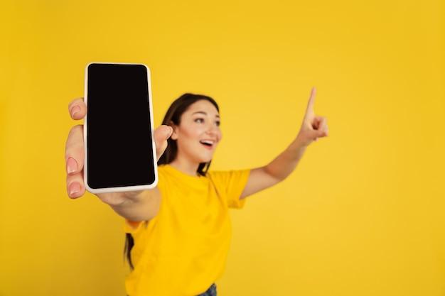 Er wordt een leeg telefoonscherm weergegeven. het portret van de kaukasische die vrouw op gele studioachtergrond wordt geïsoleerd. mooi donkerbruin model in casual. concept van menselijke emoties, gezichtsuitdrukking, verkoop, advertentie, copyspace.