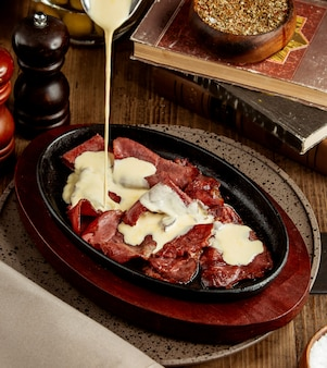 Er wordt room bovenop de rauwe gekookte plakjes vlees gegoten