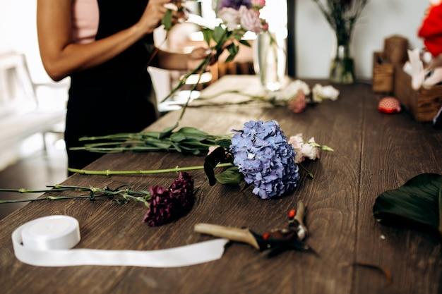 Er zijn hortensia-anjer en andere bloemenschaar en lint op de tafel in de bloemenwinkel