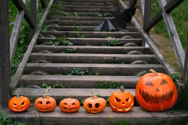 Er zijn jack o lantern-pompoenen met verschillende emoties uitgehouwen op de oude houten treden