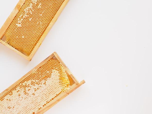 Er zijn maar weinig honingraten in frames op een witte achtergrond plat leggen kopie ruimte