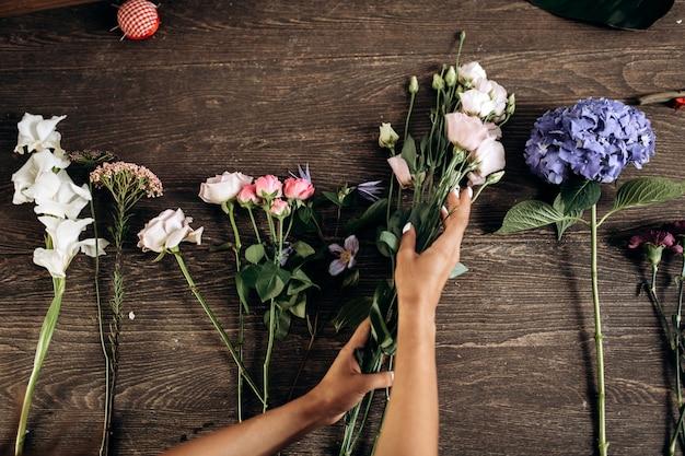 Er zijn verschillende bloemen voor het verzamelen van een boeket op de houten tafel in de bloemenwinkel