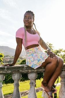 Erg blij lachende zwarte afrikaanse vrouw zittend op een tuinhuisje in een openbaar park op een zonnige dag met blauwe lucht. levensstijl van zwarte modevrouw