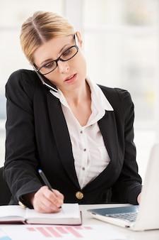 Erg druk. ernstige volwassen vrouw in formalwear die op de mobiele telefoon praat en iets in notitieblok schrijft terwijl ze op haar werkplek zit
