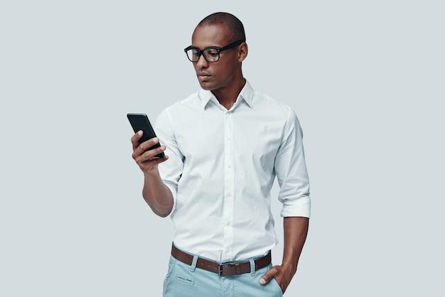 Erg druk. knappe jonge afrikaanse man die slimme telefoon gebruikt terwijl hij tegen een grijze achtergrond staat