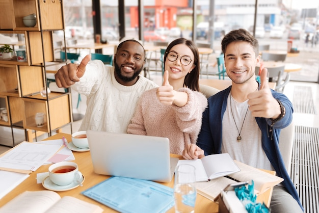 Erg goed. drie gelukkige internationale studenten houden duimen omhoog terwijl ze in café zitten en studeren.