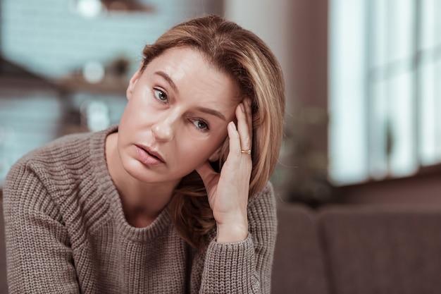 Erge hoofdpijn. blondharige gestresste vrouw met sterke hoofdpijn na groot gevecht met echtgenoot