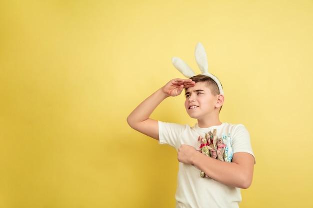 Ergens naar uitkijken. decoreren. blanke jongen als paashaas op gele achtergrond. gelukkige pasen-groeten. prachtig mannelijk model. concept van menselijke emoties, gezichtsuitdrukking, vakantie. copyspace.