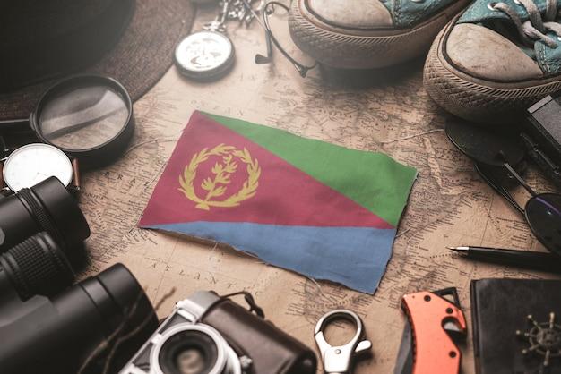 Eritrea-vlag tussen de accessoires van de reiziger op oude vintage kaart. toeristische bestemming concept.