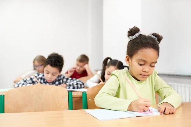 Ernstig afrikaans meisje tijdens het bestuderen op school