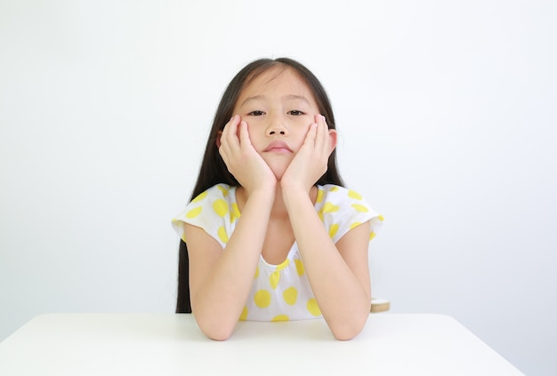 Ernstig aziatisch klein kindmeisje dat kin op handen rust met camera op tafel op witte achtergrond