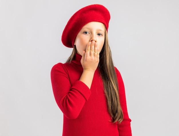 Ernstig blond meisje met een rode baret die een verrast gebaar toont dat op een witte muur met kopieerruimte wordt geïsoleerd
