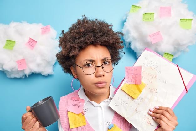 Ernstig boos, ontevreden schoolmeisje met afro-haar bereidt zich voor op wiskunde-examen maakt aantekeningen probeert zich formules te herinneren, drinkt koffie draagt ronde bril poseert tegen blauwe muurstickers rondom
