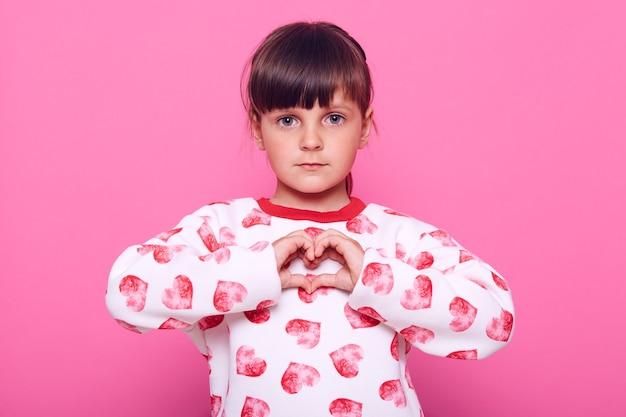 Ernstig donkerharig klein meisje dat hartgebaar toont en recht naar voren kijkt, liefde en oprechte gevoelens uitdrukt voor iemand die over roze muur wordt geïsoleerd