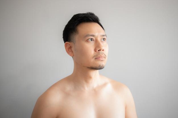 Ernstig en spanninggezicht van de aziatische mens in topless portret dat op grijze achtergrond wordt geïsoleerd.