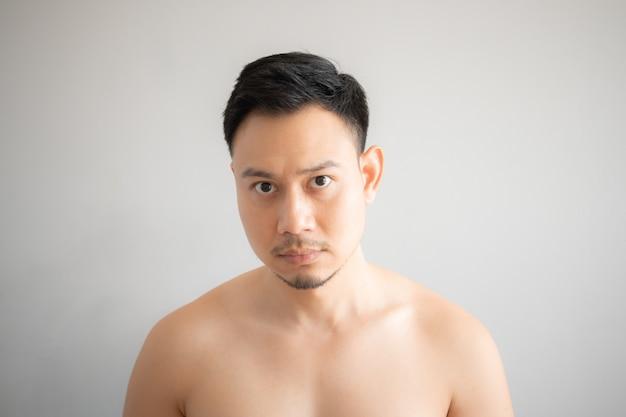 Ernstig en spanninggezicht van de aziatische topless mens