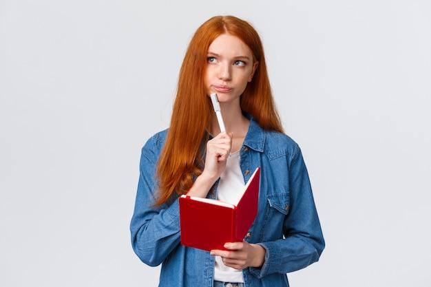Ernstig en vastberaden bazig schattig roodharig meisje met notitieboekje, pen vasthouden, grijnzend nadenkend en wegkijkend als denkend, onthoud wat kopen, boodschappen voorbereiden of to-do lijst,