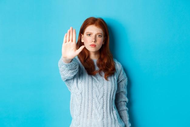 Ernstig en zelfverzekerd roodharig meisje dat zegt te stoppen, nee zegt, uitgestrekte handpalm toont om actie te verbieden, staande over blauwe achtergrond.