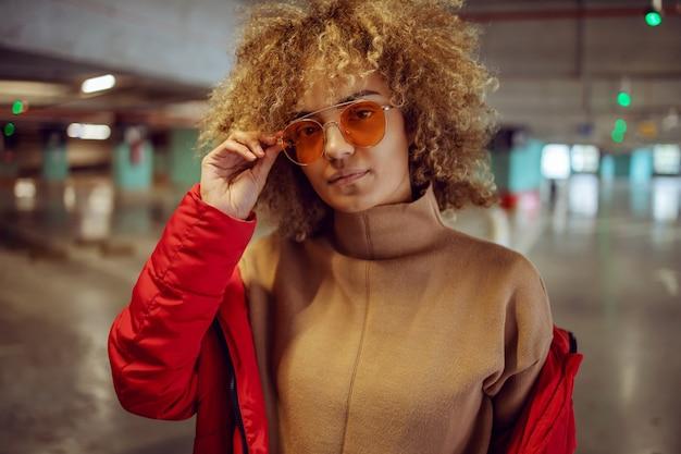 Ernstig gemengd ras hip hop meisje in jasje permanent in garage en zonnebril aanpassen tijdens het kijken naar de camera.