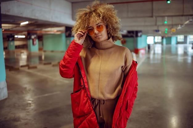 Ernstig gemengd ras hiphopmeisje in jas die zich in garage bevindt en zonnebril aanpast.