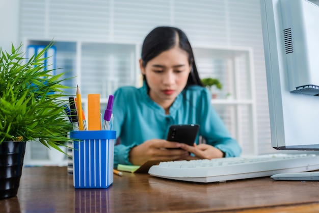 Ernstig gezicht, op zoek naar mobiele smartphone-scherm. jonge aziatische vrouw die van huis na coronavirus (covid-19) pandemie in de wereld werkt.