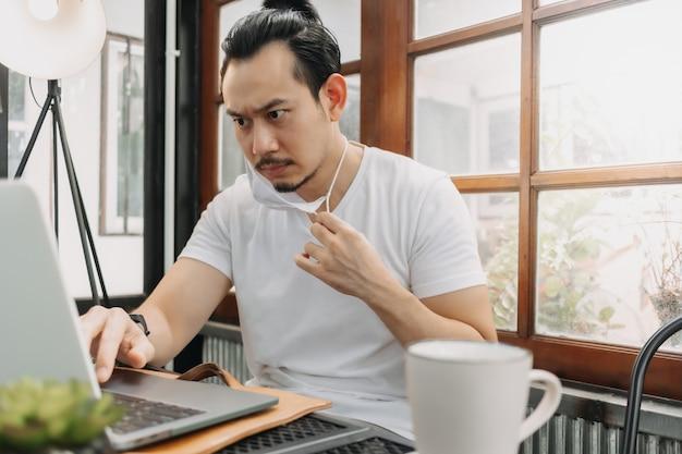 Ernstig gezicht van de mens concentreert zich op zijn werk op de laptop